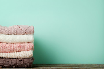 Stack of knitted sweaters on mint background