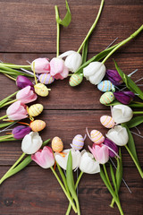 Bouquet of tulips with easter eggs on brown wooden table