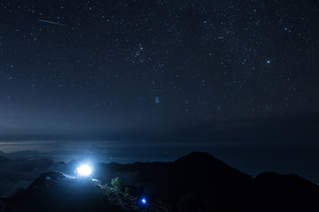 light from guide in the journey to the summit among the stars above the horizon from Rinjani, Indonesia
