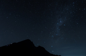 people is climbing the mountain peak in the dark night with the sky full of the stars at Rinjani
