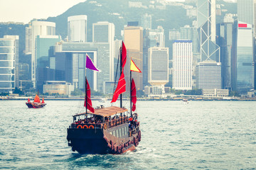 Scenic daytime skyline of Hong Kong island with skyscrapers and traditional boats sailing.