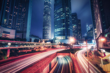 Scenic skyline of downtown Hong Kong with skyscrapers and highways at night. Colourful travel background.