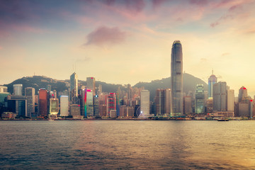 Scenic skyline of Hong Kong island with skyscrapers. Victoria harbor at sunset. Colourful travel background.