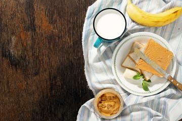 Healthy breakfast. Sandwiches peanut butter, banana, milk top view