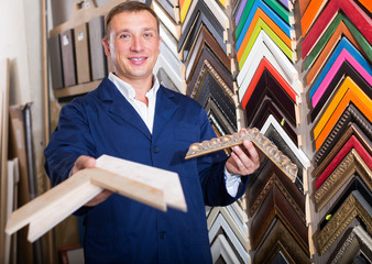 man seller in picture framing studio with wooden details
