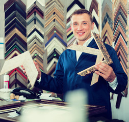 professional man seller in picture framing studio with wooden de
