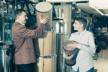 Father and teenage son examining ethnic drums