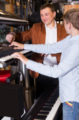 Man with  son select a synthesizer