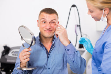 Female specialist is analysing skin of patient with using mirror before the procedure