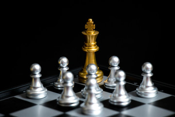 Gold King in chess game face with the another silver team on black background (Concept for company strategy, business victory or decision)