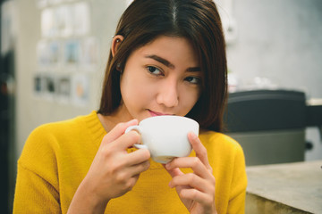 Protrait of Asian young female with long black hair holding and tasting her coffee in the coffee shop on weekend with good vibes. Tasting coffee in modern small shop. Food and drink industry concepts.