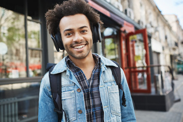 Attractive dark-skinned smiling guy with bristle, listening to music while walking on street, being in good mood and thinking about new moves while on his way to dancing studio where he works