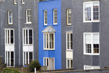 A vibrant blue painted house amongst grey slate at Tenby, Pembrokeshire, Wales, UK