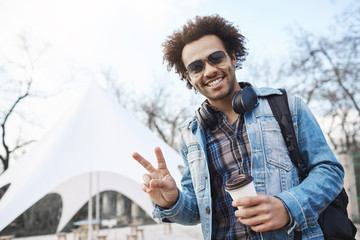 Positive handsome dark-skinned male with afro hairstyle showing peace or victory gesture while strolling across city, drinking coffee and listening music, wearing denim coat and checked shirt