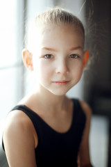 Close up portrait of a little adorable young ballerina in black sportwear near the window in sunlight