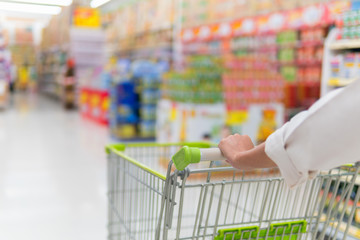 Woman pushing shopping cart in supermarket store abstract blur background with shopping cart, Supermarket aisle with empty shopping cart