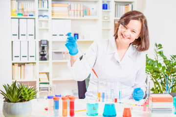 smiling female scientist pipettes colorful sample in laboratory. researcher in the laboratory. reagent flasks and test tubes with colored chemical reagents. Personalized medicine and vaccine concept.
