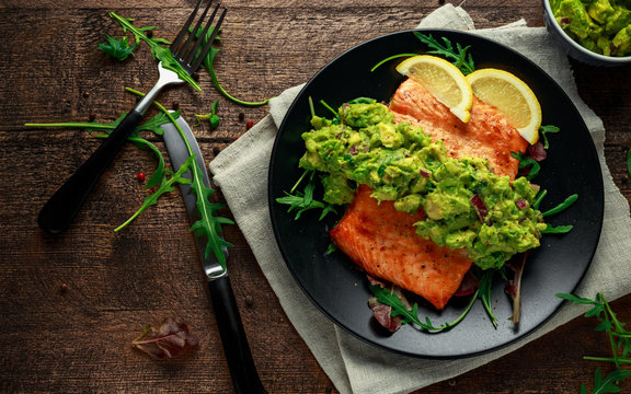 Oven cooked salmon steak, fillet with avocado salsa and green on black plate. wooden table. healthy food