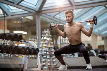 Sporty man holding heavy barbell on shoulders during physical exercise