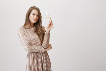 Portrait of sexy fashionable woman in glittering evening dress, holding champagne, frowning and being suspicious or worried while looking at camera and standing against gray background.