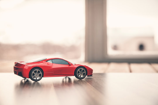 Red toy car on wood.