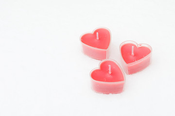 Theree small pink candles in form hearts on snow white background,