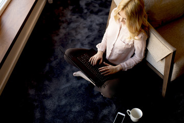 Pretty young woman using laptop and sitting on the floor