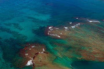 Aerial view of Pacific Ocean shoals and surf off the Hawaiian Island of Oahu, near Honolulu, shot from a small, low-flying prop plane