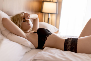 Charming sexy woman in lingerie lying on the bed
