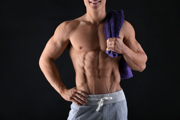 Handsome muscular young man with towel on black background