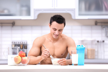 Handsome muscular young man having healthy breakfast in kitchen