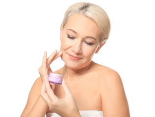 Portrait of beautiful mature woman with jar of cream on white background. Skin care concept