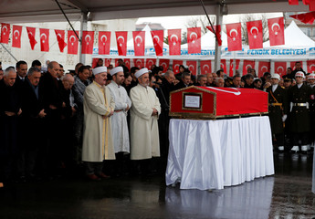 People pray behind the flag-wrapped coffin of Koray Karaca, a Turkish soldier who was killed during the operation against Syria's Afrin region, during his funeral ceremony in Istanbul