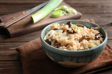 Bowl with delicious risotto and mushrooms on table