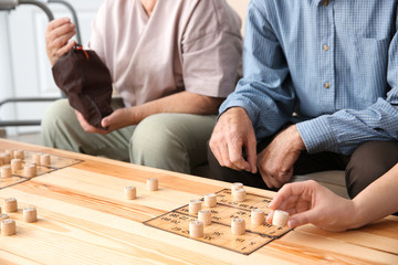 Senior people playing bingo with young caregiver at home, closeup
