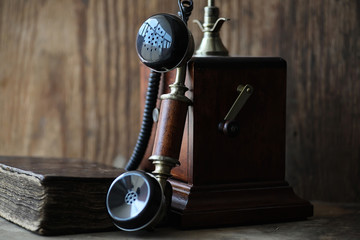 Old telephone and retro book on a wood