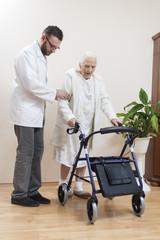 Obraz 2.Staruszka uczy się chodzić przy pomocy balkonika rehabilitacyjnego  przy asekuracji lekarza. - fototapety do salonu