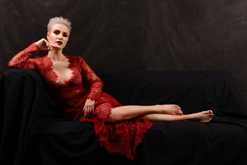 insanely beautiful short-haired young blonde woman in red lace dress lying on the couch