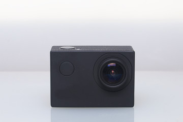 The action camera lies on a white surface.