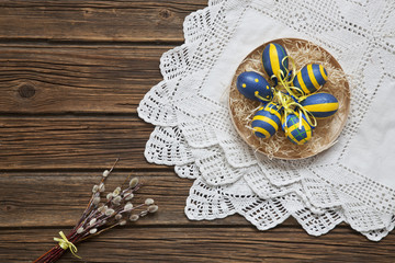 Easter eggs on a plate. Easter serving of the festive table. Top view, space for your text on a rustic wooden background