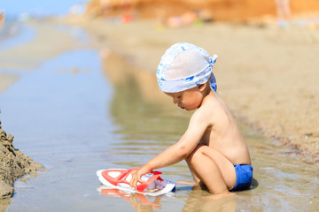Baby boy sitting on the beach near the water and plays with a toy ship