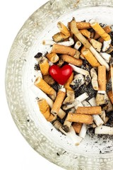 Cigarettes in a glass ashtray on a white background. Treatment of lung cancer. Tobacco industry.