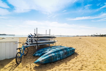 Bike, kayaks and surfboards on the sand