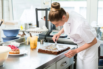 Confectioner woman getting chocolate cake ready with topping put on