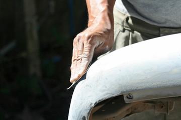 Automotive paint technician using grinder paper on car bumper,As part of the procedure to paint a new bumper car.