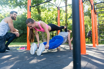 Competitive young woman and her workout partner doing couple push-up exercise during outdoor training with their friend in a modern fitness park