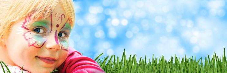 glückliches geschminktes Kind in einem Freizeitpark liegt auf Rasen mit sommerlichem Hintergrund