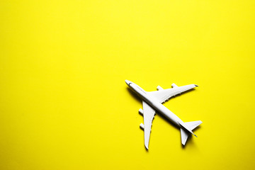 Poster Airplane Miniature toy airplane on yellow background. Trip by airplane.