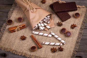 Sweet wafers rolls,  caramel candies and chocolate on a burlap