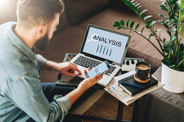 Young man, entrepreneur, freelancer sits at home on couch at coffee table, uses smartphone, working on laptop with inscription analysis on screen.Online marketing,education, e-learning.